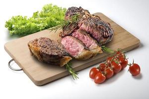 fiorentina t-bone steak gesneden op een rechthoekige houten snijplank en groenten