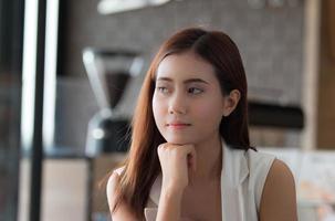 Aziatisch meisje dat bij een coffeeshop met laptop werkt foto