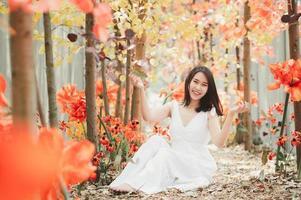 Aziatische vrouw in een witte jurk bladeren gooien zittend in het park foto
