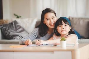 gelukkige Aziatische familie moeder en dochter samen studeren foto