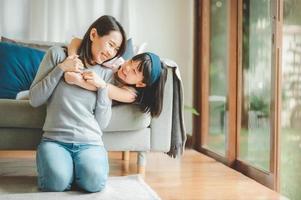 gelukkige Aziatische moeder en schattige kleine dochter met plezier foto