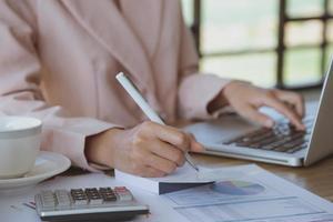 jonge zakenvrouw die op laptop op haar werkstation werkt foto