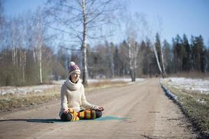 een jonge atletische vrouw voert buiten yoga- en meditatieoefeningen uit foto