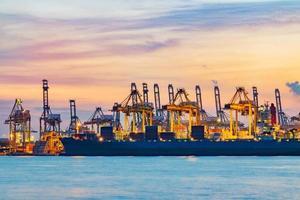 vrachtschip dat lading laadt bij laaddok in singapore bij schemering