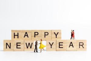 miniatuurmensen dansen op houten blokken met de tekst gelukkig nieuwjaar op een witte achtergrond foto