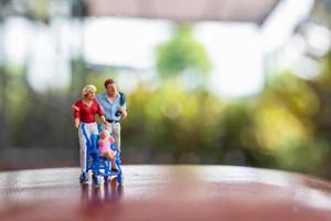 miniatuurouders met kinderen die buiten lopen, gelukkig familieconcept foto