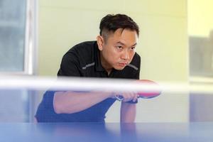 mannelijke tafeltennis met racket en bal in een sporthal foto