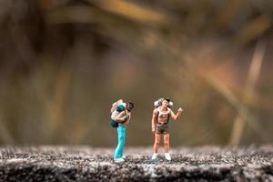 miniatuur backpackers die zich op een betonnen vloer met een bokeh-aardachtergrond bevinden