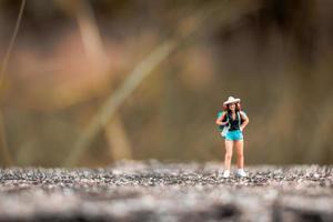 miniatuur backpacker staande op de betonnen muur met natuurlijke achtergrond