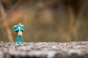 miniatuur backpacker staande op een betonnen vloer met een bokeh natuur achtergrond