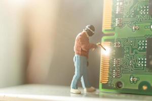 miniatuur computeringenieur die computerhardware, technologieconcept herstelt foto