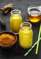 gouden melk met kaneel, kurkuma, gember en honing op zwarte betonnen achtergrond