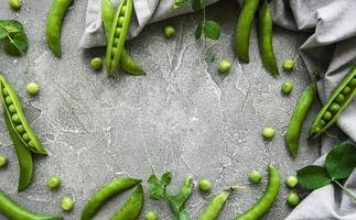 peulen van groene erwten op een concrete achtergrond