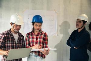 jong Aziatisch paar dat in harde hoeden huisplannen met ingenieur onderzoekt