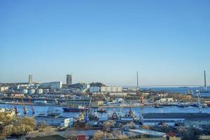 stadsgezicht van een haven en de Russische brug met een heldere blauwe hemel in Vladivostok, Rusland foto