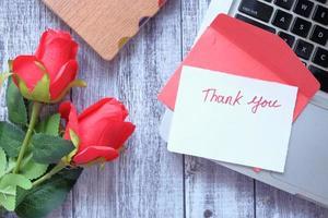 bedankje en envelop op houten tafel foto