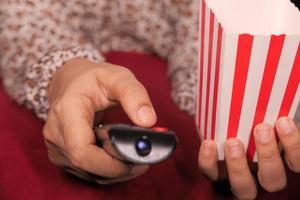 close-up van vrouw hand met afstandsbediening tv