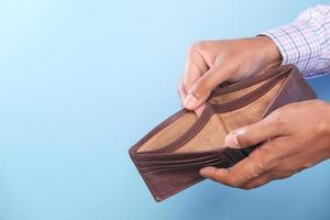 hand met lege portemonnee met blauwe kopie ruimte foto
