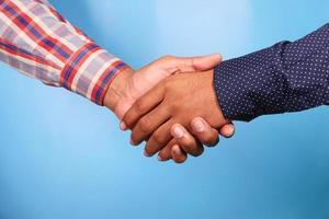 twee mensen handen schudden tegen blauwe achtergrond foto