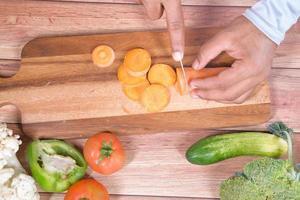 snijden van verse wortelen op snijplank foto