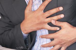 jonge man die pijn in het hart lijdt en de borst met de hand vasthoudt