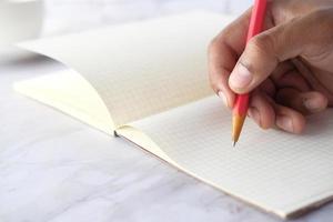 close-up van man hand schrijven met potlood op grafiek briefpapier foto