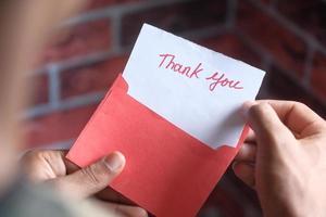 persoon die een bedankkaart opent foto