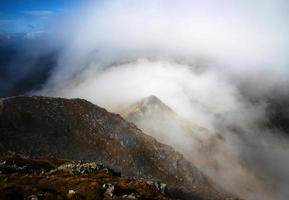 mist die over de top van de berg ligt foto