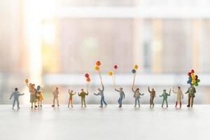miniatuurmensen die met ballons lopen, gelukkig familieconcept foto