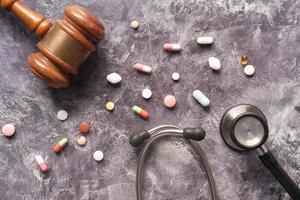 bovenaanzicht van hamer, stethoscoop en pillen op grijze achtergrond foto