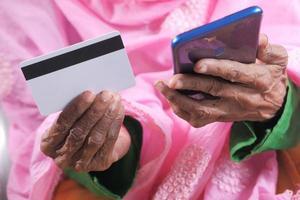 handen van de senior vrouw online winkelen