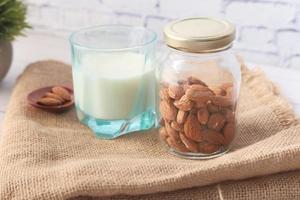 amandelen en plantenmelk op neutrale achtergrond foto