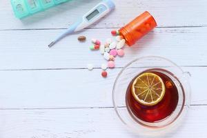 citroenthee, pillen en thermometer op een houten tafel