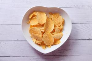 kom met chips op houten achtergrond