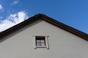 onderdeel van een rieten dak van een dorpshuis met een bewolkte blauwe hemel foto