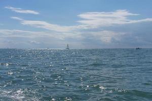 zeegezicht met verre boten in een watermassa tegen de bewolkte blauwe hemel in Sochi, Rusland foto
