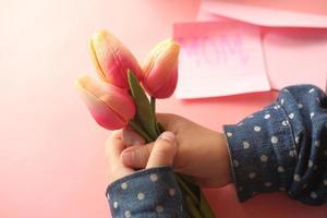 kind hand met tulp bloem
