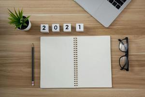 lege papieren notitieblok met jaarnummer 2021 voor planning op houten tafel achtergrond foto