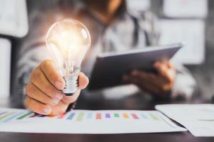 succesvol bedrijfsidee en creatief innovatieconcept, de holdingslamp en tablet van de close-upzakenman foto