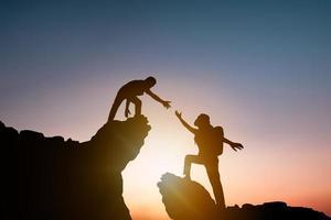 silhouet van persoon die andere wandelaar helpt een berg te beklimmen