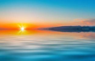 kleurrijke oranje zonsondergang en bergen naast een kalme zee foto