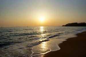 zonsondergang over bergen en water op een strand foto