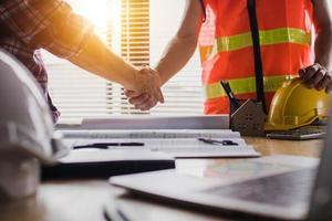 handdruk van twee zakenlieden na het plannen van blauwdruk foto