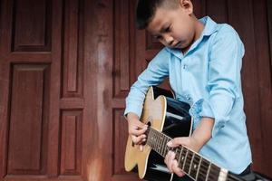 jongen een akoestische gitaar spelen foto