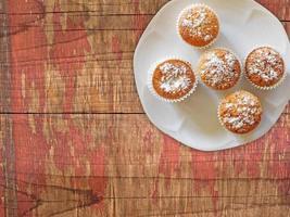 muffins op een witte plaat op een houten tafel achtergrond foto