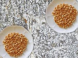 pinda's op twee witte platen op een rots of stenen muur achtergrond