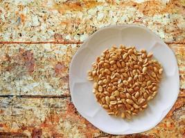pinda's op een witte plaat op een houten tafel achtergrond