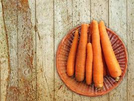 wortelen in een rieten mand op een houten tafel achtergrond foto
