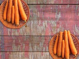 wortelen in twee rieten manden op een houten tafel achtergrond foto
