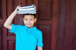 jongen met boeken op zijn hoofd